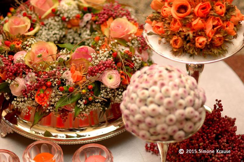 Floralkugeln und ein Blütenkranz in warmen Farben