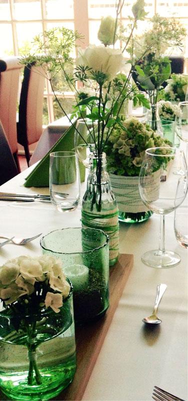 Grünes Glas und Eichenbretter als Begleitung für die weißen Blüten